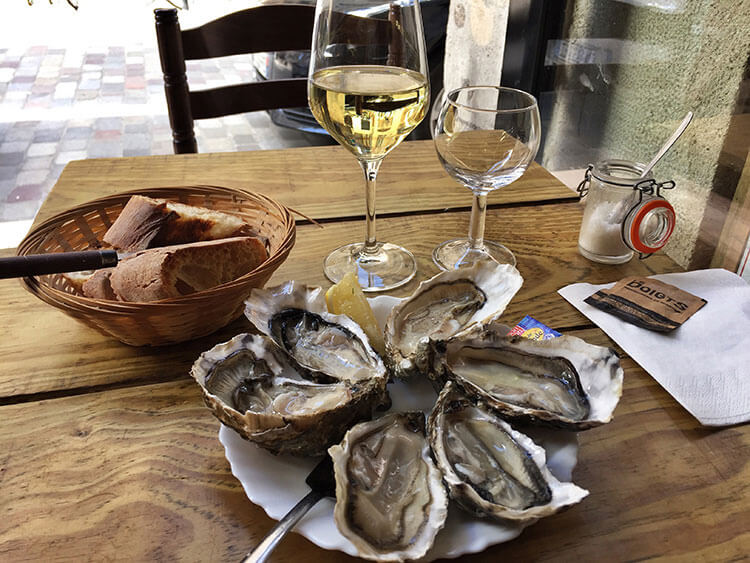 A plate of half a dozen Cap Ferret oysters and a glass of white Bordeaux