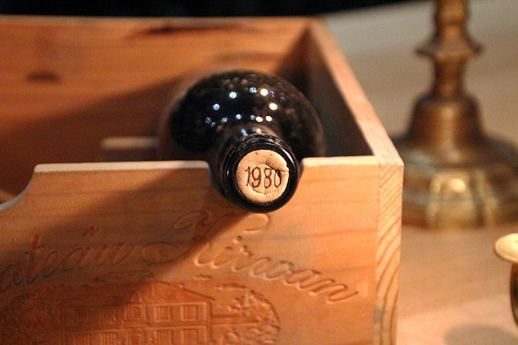 A bottle of 1980 Château Kirwan 1855 Grand Cru Classé sits in a wine box