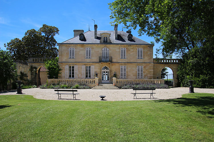 The main house of Chateau Kirwan with a park and benches looking at it