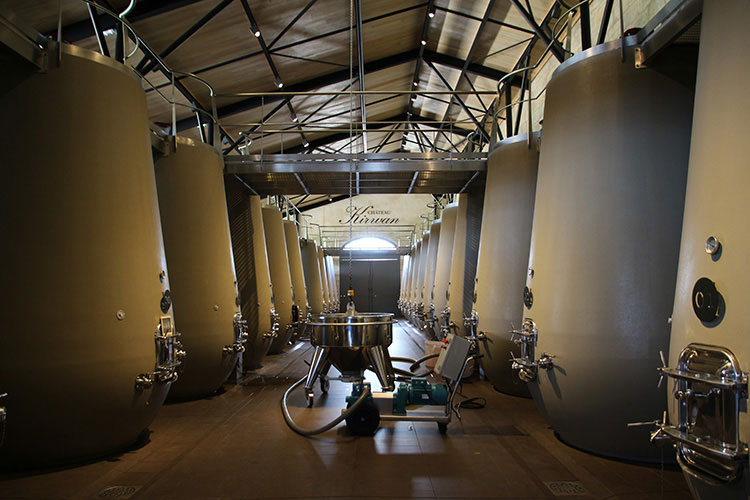 Inside the winery with large concrete tanks used to ferment the wine at Château Kirwan