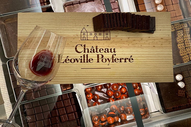 A wine glass laying flat on a Château Léoville-Poyferré board with Hasnaâ chocolats