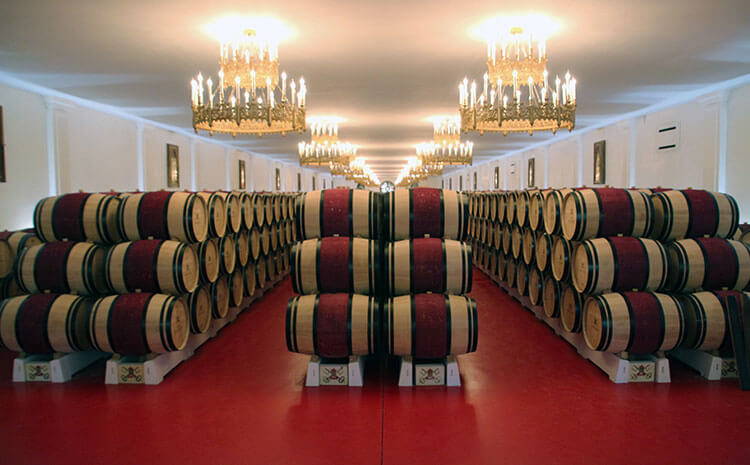 Three rows of barrels with a center stripe of red sit stacked in Château Pape Clement's barrel room
