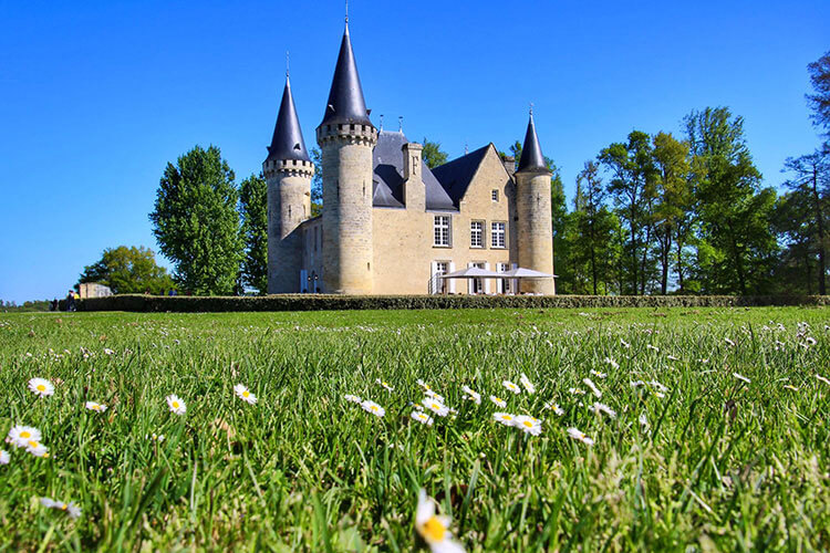 The castle of Chateau d'Agassac with white daisies in the grass on a sunny day