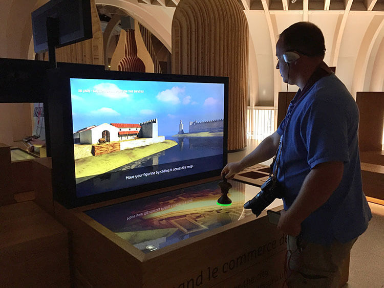 Tim uses a game piece to learn about the history of Bordeaux monuments at La Cité du Vin