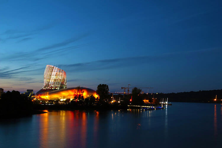 The wine decanter shaped La Cité du Vin lit up at dusk with a light show in orange and reds in Bordeaux, France