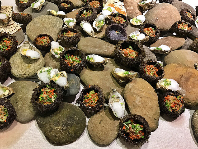 Raw oysters and sea urchin appetizers are arranged on a bed of rocks at Ciné Gourmand at La Cite du Vin