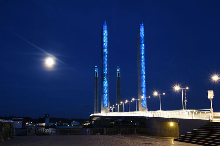 Pont Jacques Chaban-Delmas is lit blue to indicate high tide at nighttime in Bordeaux, France