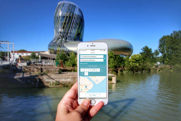 Holding an iPhone with the TBM app showing directions from La Cité du Vin with the museum in the background