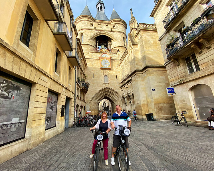 Jennifer and Tim pose on their bicycles in front of the Grosse Cloche in Bordeaux, France