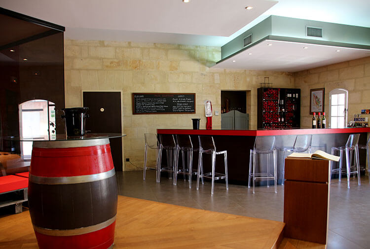 The tasting room and boutique is modern with clear plastic bar stools and a glass wall that looks in to the barrel room