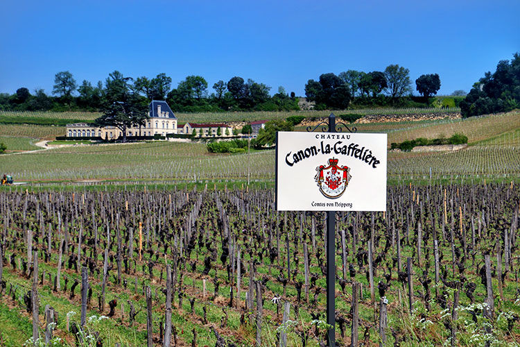 The Château Canon-la-Gaffelière sign marking a plot of their vineyards with another Saint-Êmilion château in the distance