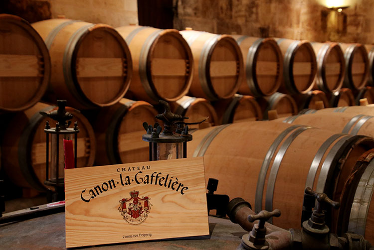 Rows of French oak barrels stacked two high in the barrel room at Château Canon-la-Gaffelière