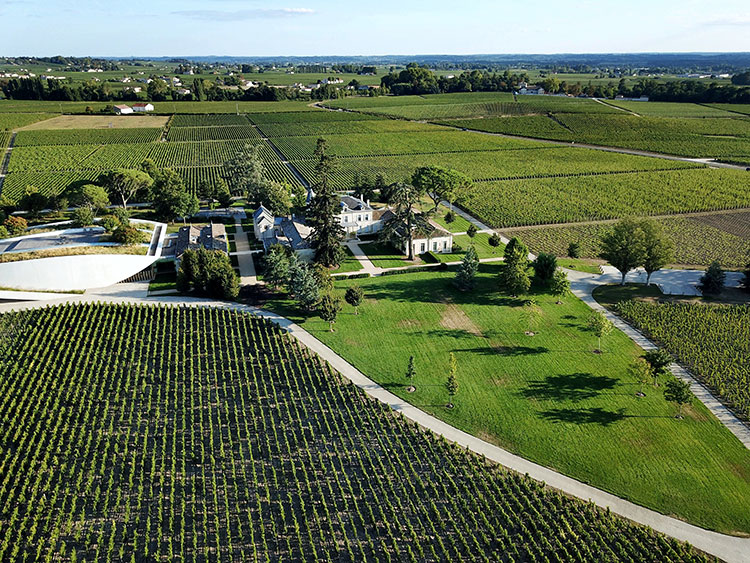 An aerial drone view of Château Cheval Blanc's castle and modern white winery surrounded by vineyards in Saint-Émilion