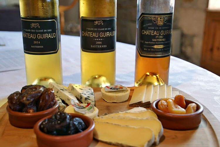 A cheese board with three cheeses, dates, apricots and prunes and bottles of the Chateau Guiraud 2014, 2006 and 1998 vintages
