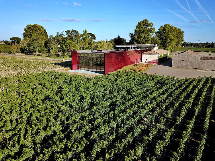 A drone shot of the vineyards and modern red winery of Château La Dominique