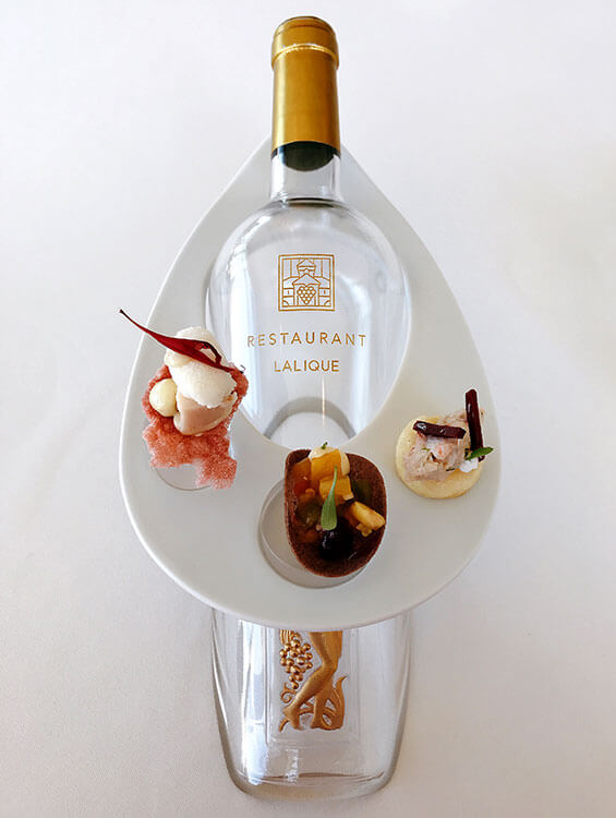 The amuse-bouche served on a porcelain plate placed on the neck of a wine bottle with chicken with a sweet wine sorbet, Marmande tomatoes with hibiscus, and lobster on a brioche