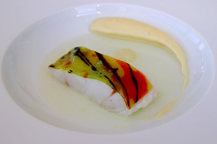"Sea bass filet topped with a red, yellow and green ""skin"" made of bergamot and harlequin at Restaurant Lalique at Chateau Lafaurie Peyraguey"