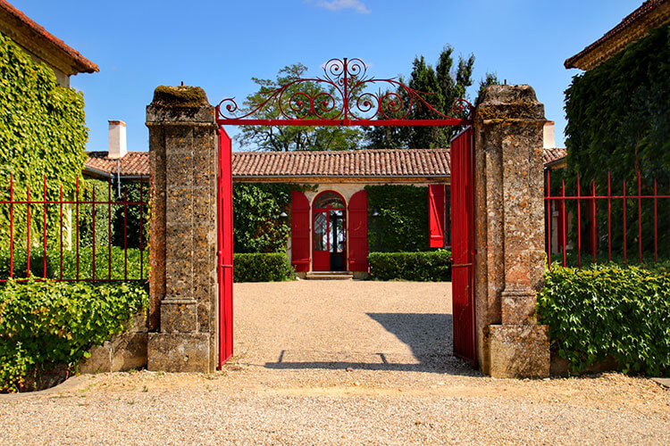 A red gate frames the single level former stone farmhouse with red doors and shutters at Chateau Sigalas Rabaud