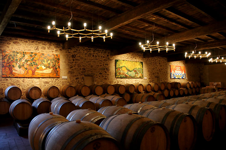 The barrel room is the old stable with wooden beams and artworks lining the stone walls at Chateau Sigalas Rabaud