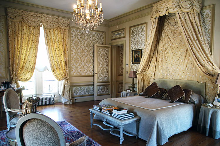 A guest room decorated in gold fabrics at Château Pape Clement in Bordeaux, France