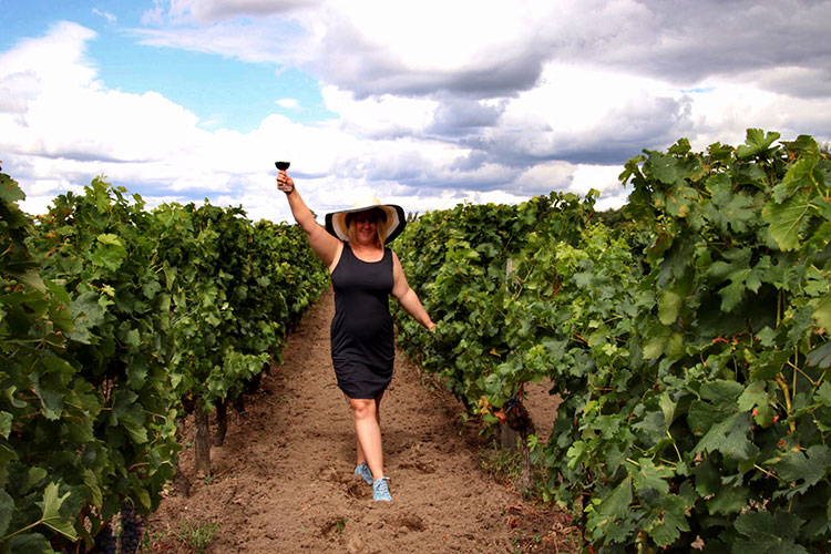 Jennifer holds up a glass of Bordeaux wine while in the vineyard in Pomerol, in the Bordeaux wine region