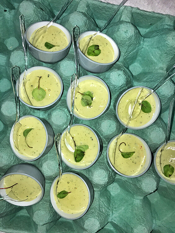 Creamy basil egg served in egg cups in an egg crate at Cine Gourmand at La Cite du Vin