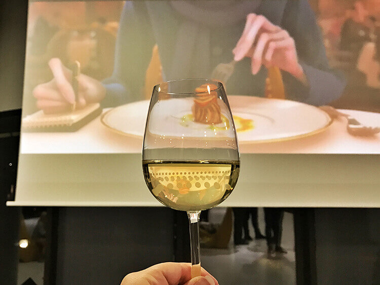 Jennifer holding a glass of white wine in front of the screen as scenes from Ratatouille play at Cine Gourmand