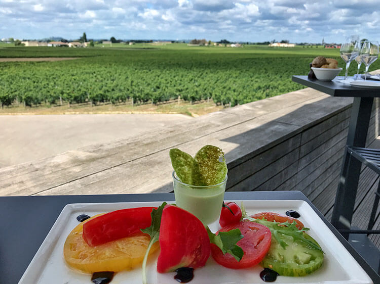 A yellow, red and green tomato salad with the vineyard view blurred behind at La Terrasse Rouge