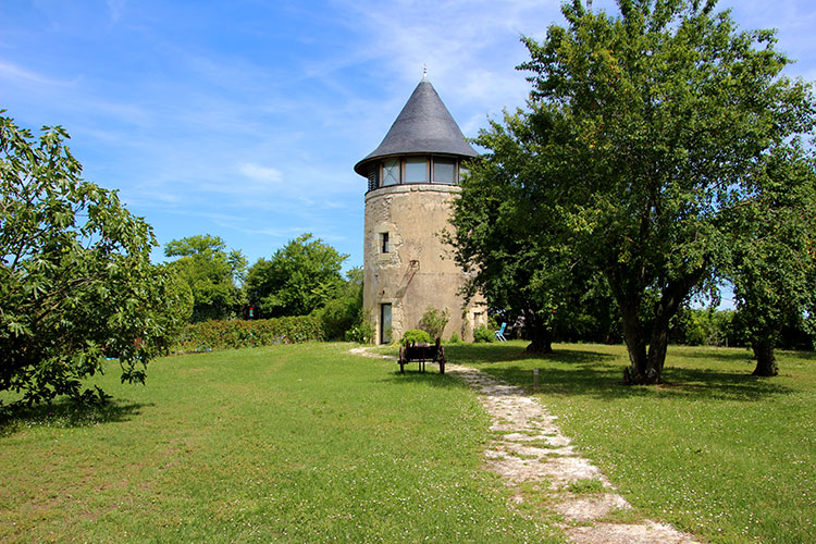 The windmill stands in a garden and next to the swimming pool in Margaux