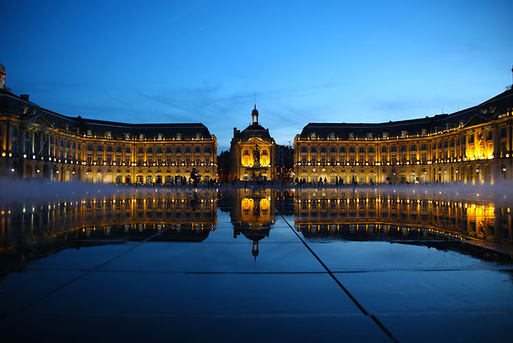 Blue hour at Bordeaux's Water Mirror with the mirror-like surface after the water drains and the mist starting to come on as the Place de la Borse is light up and reflects on the mirror