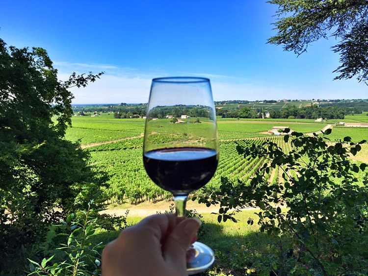 Jennifer holds up a glass of Château Haut-Sarpe in front of hills with vineyards in Saint-Emilion, France