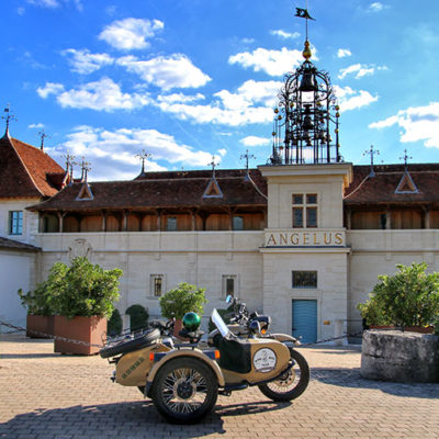 The Ural sidecar motorcycle parked in front of Château Angélus with their iconic bells