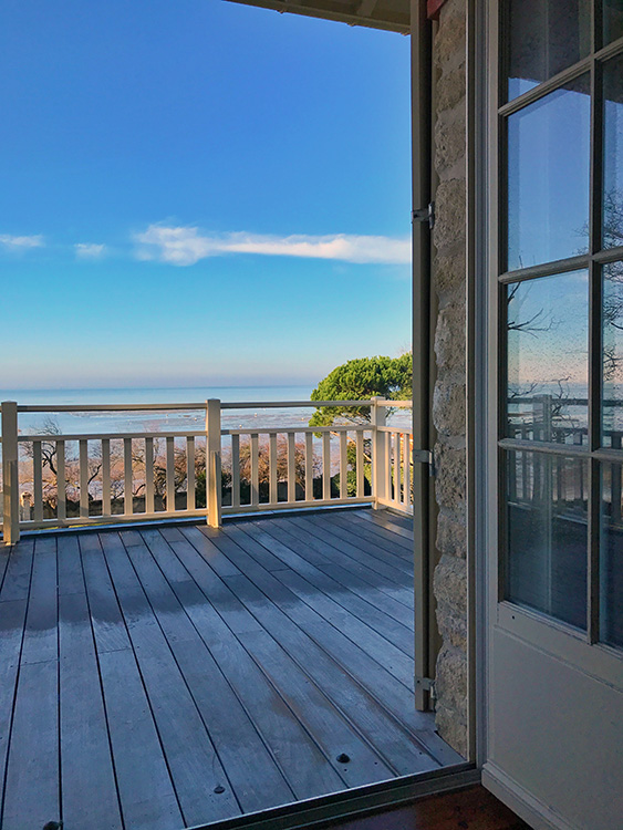 The open bedroom door and balcony overlooking the Bassin of Arcachon at Villa La Tosca