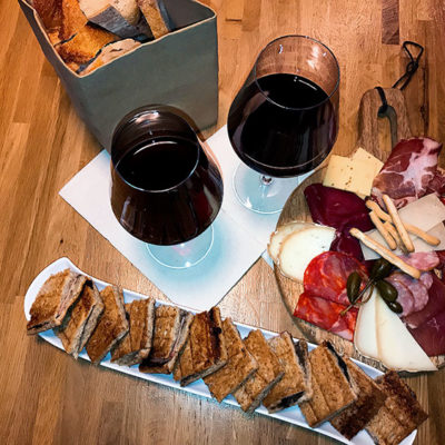 A platter with the truffle croque monsieur, a charcuterie plate and two glasses of wine at Vins Urbains