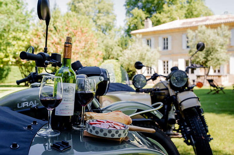 A bottle of wine with charcuterie is set up on the Ural motorcycle sidecar to enjoy along the tour through Saint-Emilion