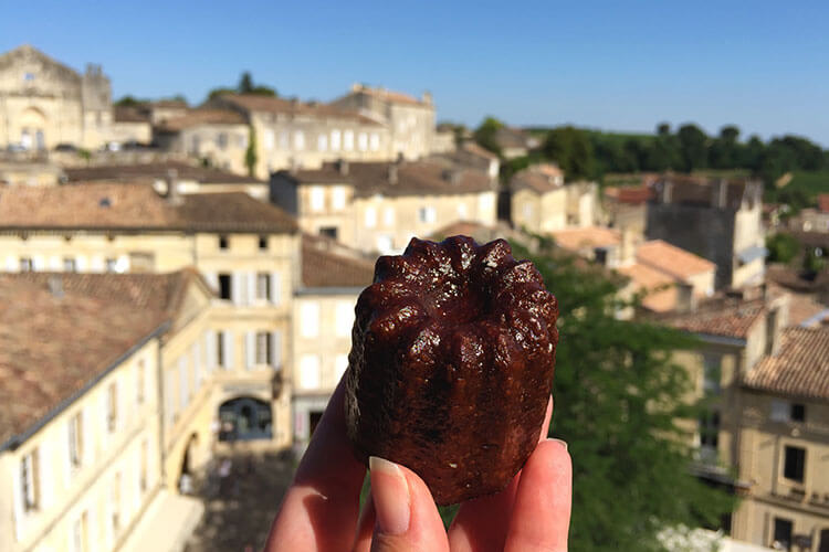 Jennifer holds up a canelé in Saint-Émilion with the village blurred behind it