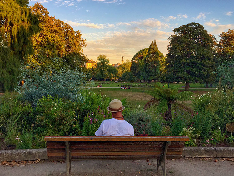 A woman sits on a bench gazing out over the great lawn of Jardin Public in Bordeaux