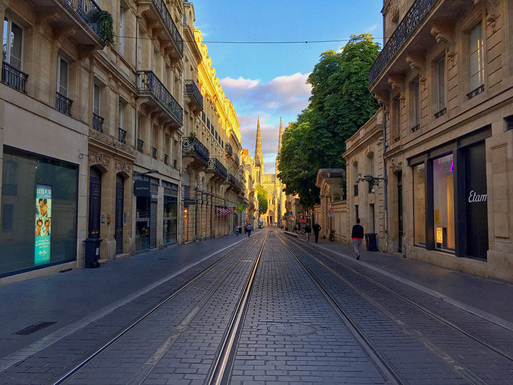 The spires of Cathedral Saint-Andre seen from looking down Rue Vital Carles at sunset