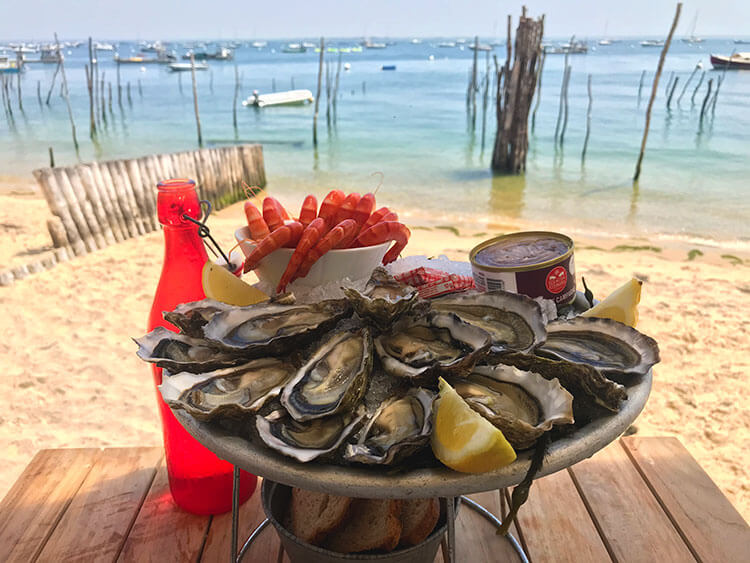 A plate of a dozen oysters on the table with the beach and Bassin of Arcachon behind at Emile et un Huîte in Village l'Herbe on Cap Ferret