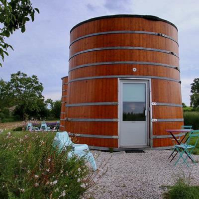 Two giant wine vats sit next to the vines at Château de Bonhoste