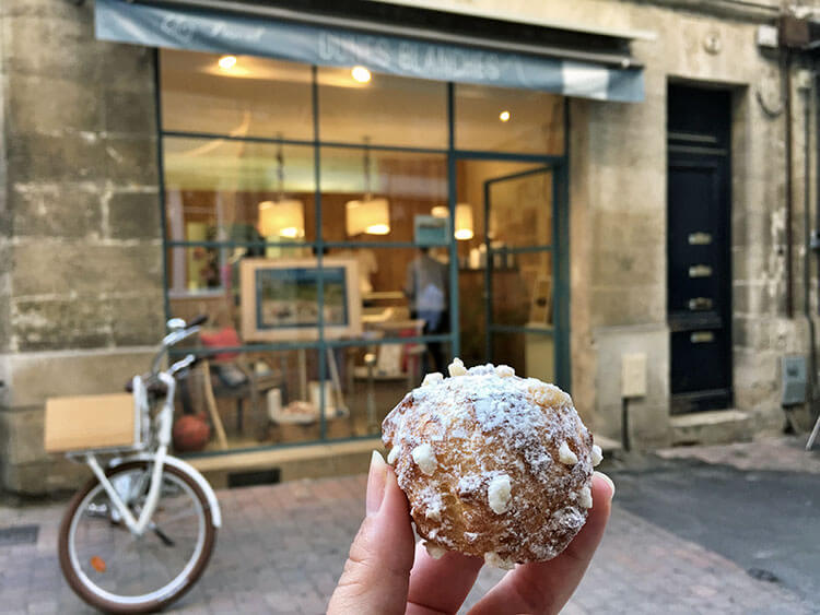 Holding up a single Dunes Blanches pastry in front of the Dunes Blanches Chez Pascal shop in Bordeaux