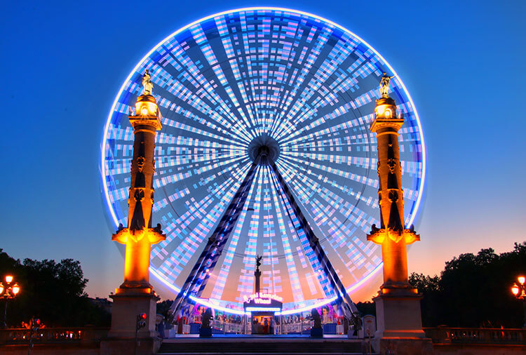 A ferris wheel all lit up at sunset on Place des Quinconces