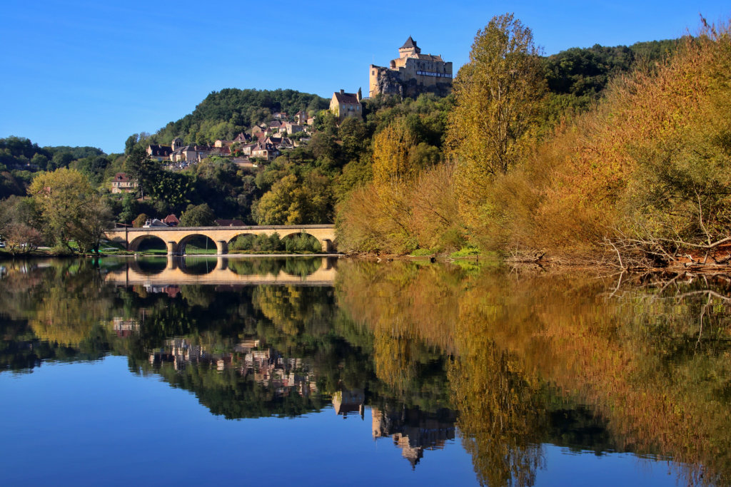 The village of Castelnaud and the Castelnaud Bridge reflect on the mirror-like Dordogne River