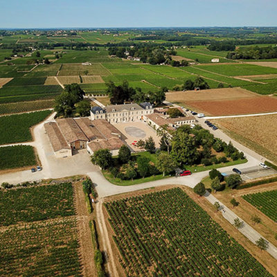 A drone aerial of the farmhouse complex of Chateau Soutard surrounded by vineyards in Saint-Émilion