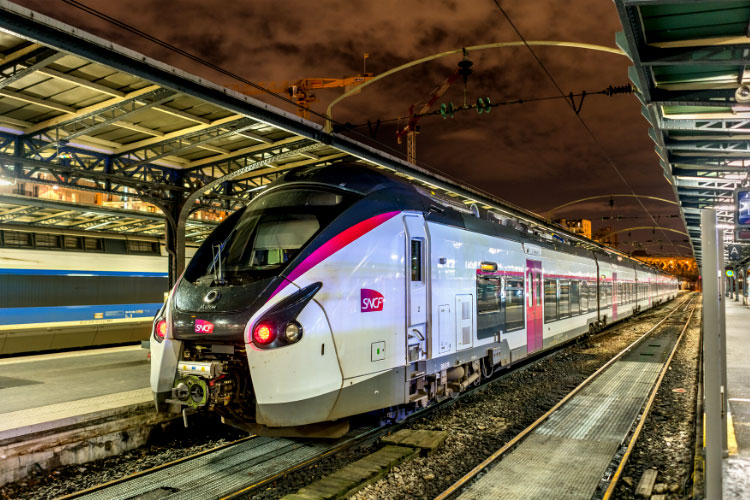A SNCF TGV train is parked at a platform in a train station