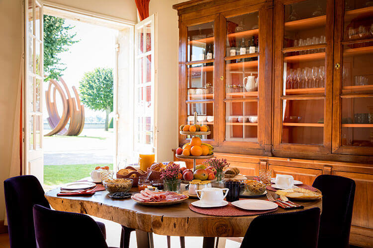 A breakfast spread of fresh fruit, meats, cheese and pastries in the dining room at Château Malescasse