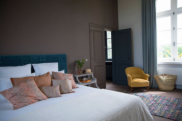 A bedroom decorated in light tones of cream with splashes of aqua looks out to the vines at Château Malescasse