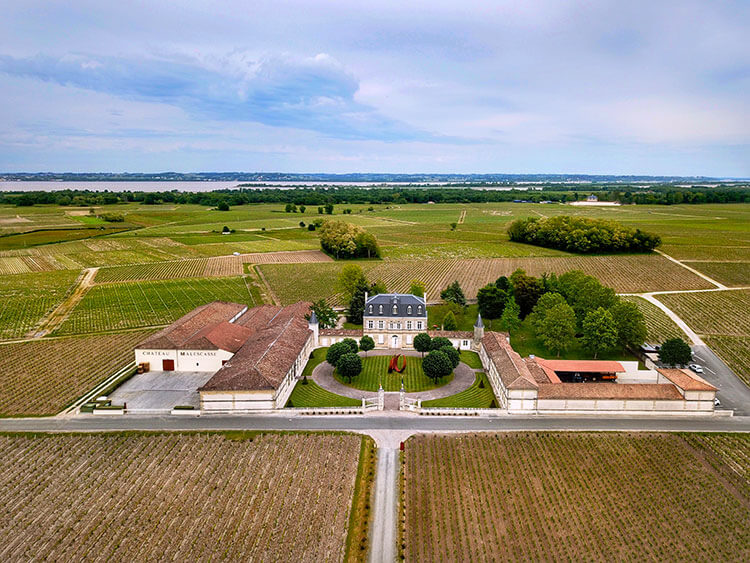 A drone aerial of Château Malescasse with the Gironde Estuary visible behind the vines