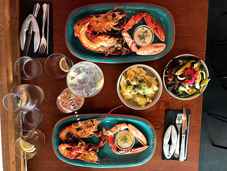 Two steamed lobsters with butter, potatoes, salad and gin cocktails at La Crique