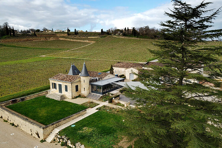 The little castle of Château de Candale with its turrets and surrounded by vineyards as seen from a drone aerial